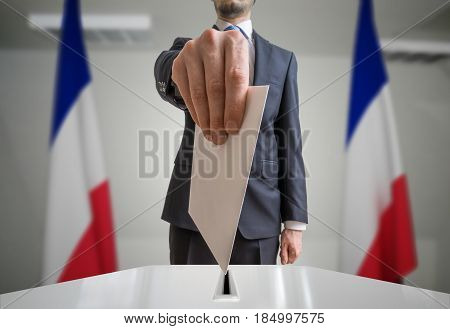 Election in France. Voter holds envelope in hand above vote ball. Wide angle photo.