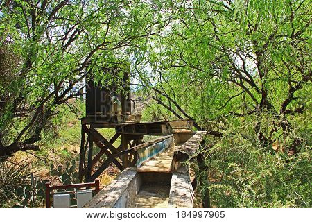 Hidden old mining sluice box with water barrel in the butterfly garden on La Posta Quemada Ranch in Colossal Cave Mountain Park in Vail, Arizona, USA near Tucson.