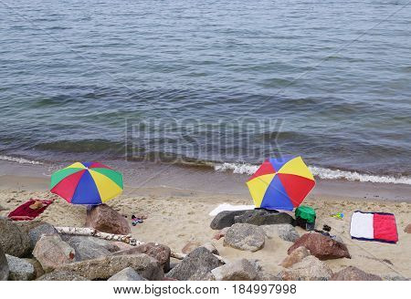 Two multicolored sunshades are on sandy beach on sea shore