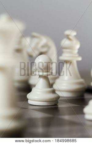 Chess figure pawn on the board. White chess figures Knight Bishop Pawn. Chessboard game in process. Teamwork and diversity concept photo. Strategy of winning. Competitive sport. Smart table game