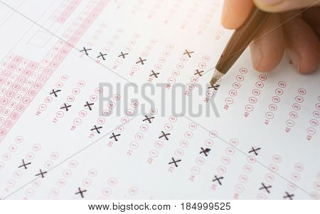student holding pen for testing in exercise exams answer sheets and checkbox for final exam test in classroom