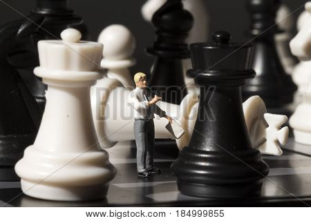 Chessman and chess king fall on game board. Playing chess with miniature doll macro photo. Man explains chess game rules. Teacher puppet on chessboard. Checkmate game in process. Chess mate finish