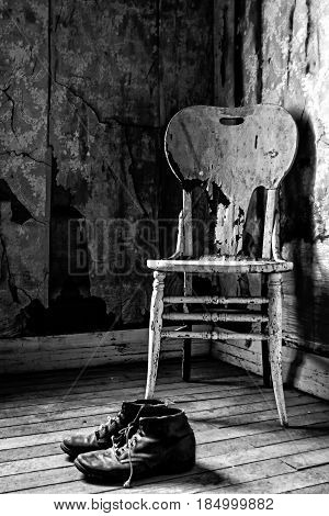 A Bygone Era Vertical, black and white photograph of a lone chair and a pair of shoes with space for text. Suitable for use in the travel and other industries, advertising, or as a wall decoration in hotels with western motif.