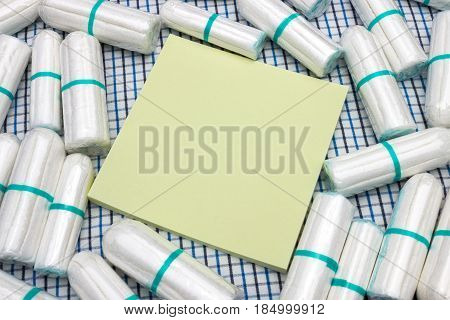 Yellow stick note and menstruation sanitary clean cotton tampons on the plaid coverlet. Woman hygiene protection. Soft tender protection for woman critical days gynecological menstruation cycle