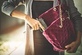 Woman pulls a gun from her swanky purse. Conceal carry weapon for protection themselves concept. Selective focus to gun. poster