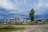 The ruins of a multistory building in the abandoned town of Yubileyny on the background of dark cloudy sky. Russia Perm Krai poster