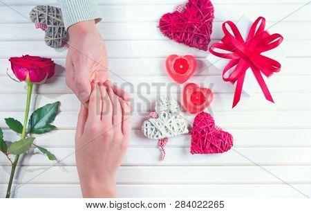 Valentine Gift. Young Couple taking hands, over wooden background. St. Valentine's Day, Love concept. Top view, tabletop. Hand in Hand, romance, dating concept, top view