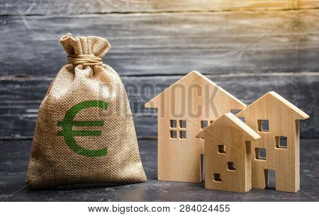 A Bag With Euro Money And Three Houses. Affordable Cheap Loan, Mortgage. Taxes, Rental Income. Build