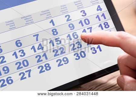 Close-up Of A Businessperson Looking At Calendar On Digital Tablet In Office