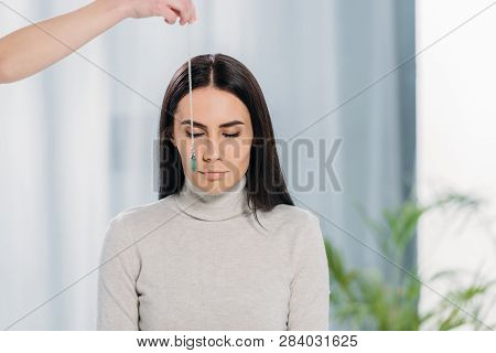 cropped shot of hypnotist with pendulum hypnotizing young woman with closed eyes poster