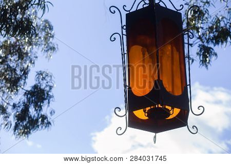 Vintage Ornate Lantern Hanging From A Tree, With A Blue Sky Background