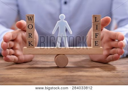 Human Figure Standing Between Work And Life Wooden Blocks On Seesaw Being Protected By Businessperso