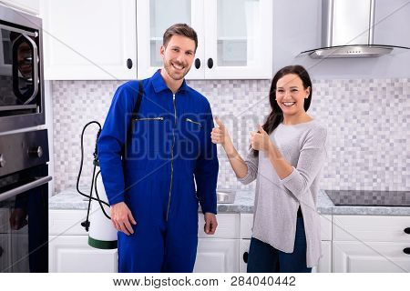 Woman Showing Thumbs Up With Pest Control Worker Standing In Kitchen