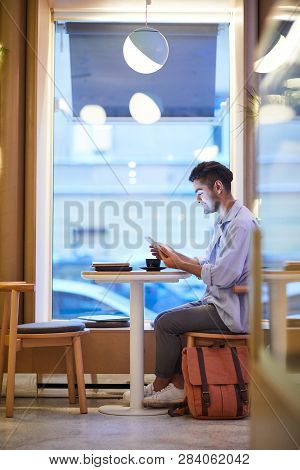 Casual Guy With Touchpad Sitting By Table In Cozy Cafe At Lesire, Having Tea, Resting And Watching O