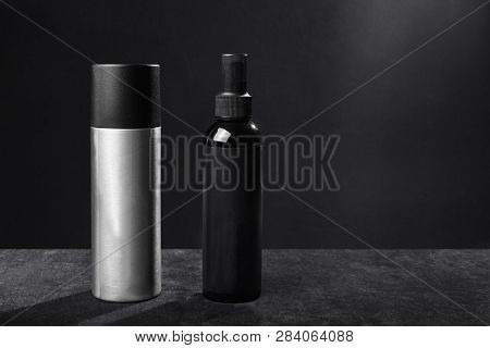 Two Flacons Of Professional Hair Spray And Mousse Standing On A Table On A Black Background. Concept