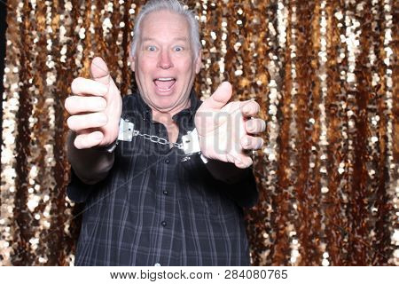 Man in a Photo Booth. A Caucasian man smiles and has fun posing in a Photo Booth with a Gold Sequin curtain. White male in plastic handcuffs looks into the camera and smiles.
