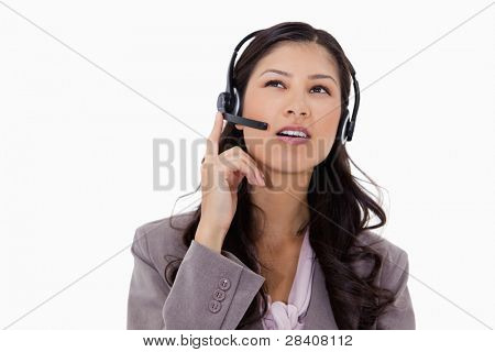 Businesswoman listening to caller with headset against a white background