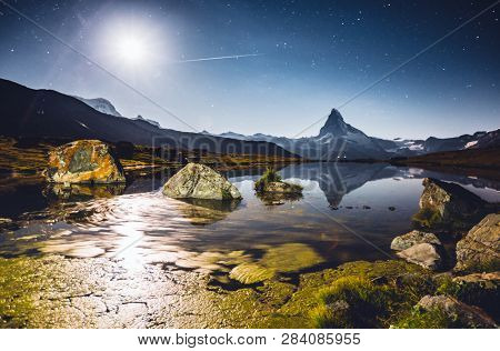 Famous peak Matterhorn (Cervino) under the starry sky. Location place Stellisee, Switzerland, Valais region, Swiss alps, Europe. Forces and beauty of untouched nature. Discover the beauty of earth.