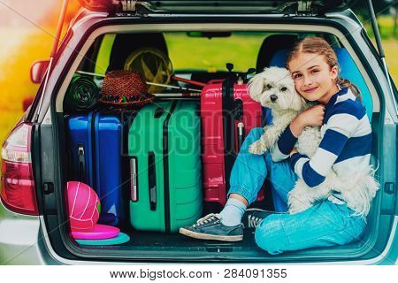 Summer vacation, young girl in car trunk with dog in the car is ready for travel for family vacation.
