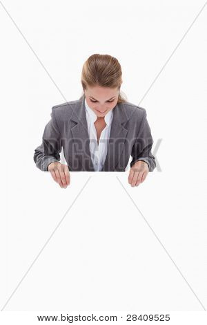 Bank employee looking down at blank sign in her hands against a white background