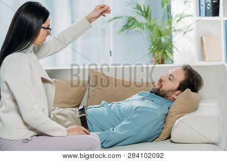 side view of young hypnotist with pendulum and bearded man with closed eyes lying in couch during hypnotherapy poster