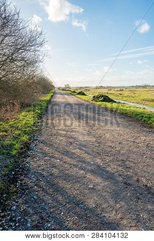 Vertical Image Of A Country Road Covered With Rubble In A Typical Dutch Polder Landscape With A Ditc
