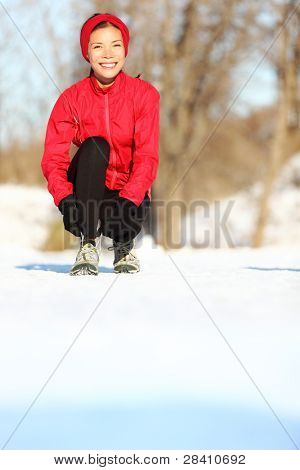 Winter runner getting ready running tying shoe laces. Beautiful young mixed race Asian / Caucasian female fitness model training outside. Copy space on snow.
