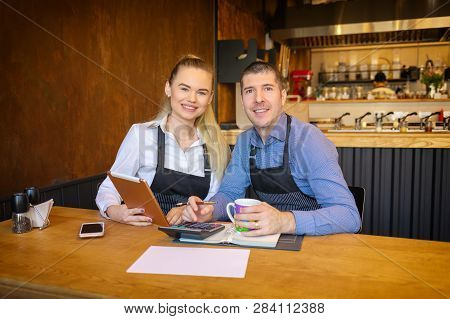 Happy Man And Woman Going Through Paperwork Together In Their Restaurant. Small Family Restaurant Ow