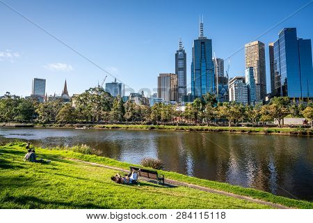 2nd January 2019, Melbourne Australia : People Resting On Yarra Riverbank Promenade Grass In Central
