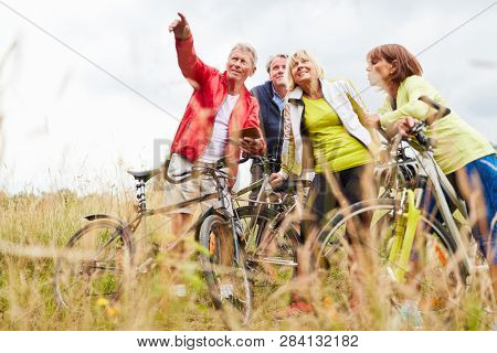 Senior citizens use a smartphone app with GPS for navigation on their bike tour