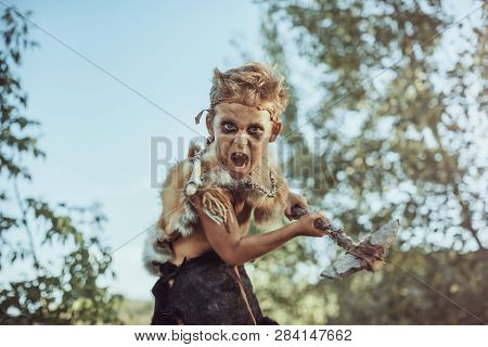 Caveman, Manly Boy With Weapon Aggressively Shouting. Dramatic Action Photo Of Young Primitive Boy O