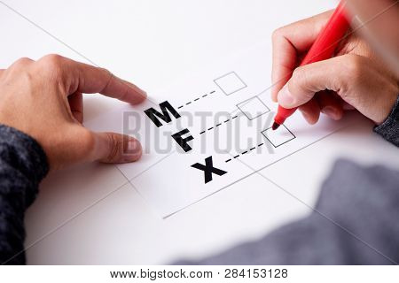 closeup of a young caucasian person about to mark on the X in a form with the letters M for male, F for female and X for the third gender category