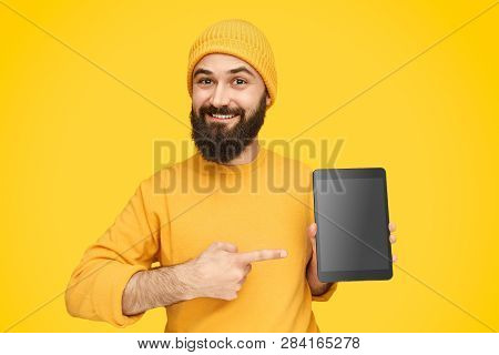 Happy Bearded Hipster In Yellow Outfit Pointing At New Touchpad Doing Promotion On Yellow Background