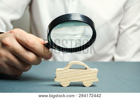 A Man Holds A Magnifying Glass Over A Miniature Wooden Car. The Estimated Cost Of The Auto. Analysis