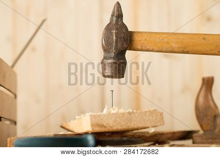 Big Nail. A Man In White Gloves Is Hammering A Big Nail On The Desk With Black Background. Shiny Scr