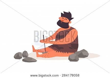 Primitive Man Produces Fire By Friction. Prehistoric Man Dressed In Pelt On A White Isolated Backgro