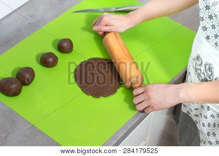 Female Hands Roll A Dough With A Wooden Roller On A Green Silicone Coffee Table Lying On The Kitchen