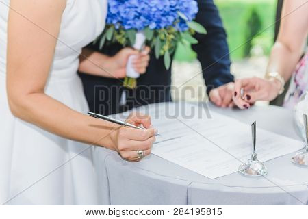 Wedding Day. Bride Signs On Marriage Certificate. Horizontal Frame