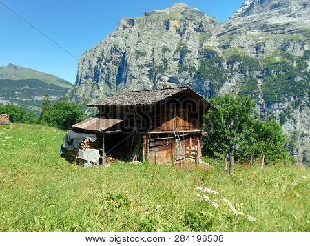 A Log Cabin With A Supply Of Cut Wood For The Fire Place In The  Mountains Of Switzerland.