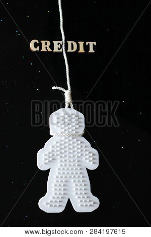A CREDIT word is laid out wooden letters. A plastic man hung himself on a rope. Credit history and suicide. Credit crunch and credit suicide. Credit slavery. Interest on credit