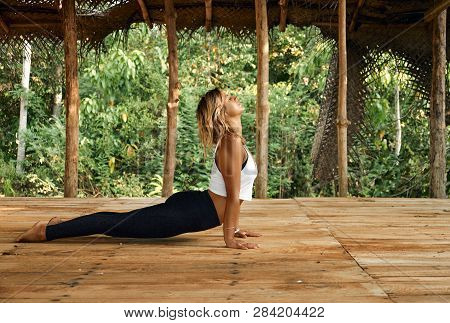 Woman Practicing Yoga In Tropical Open Yoga Studio Place