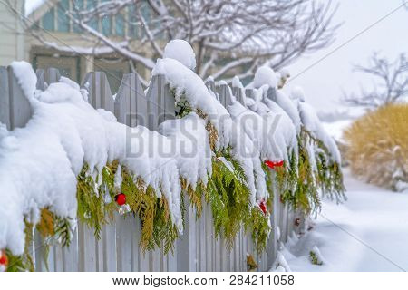 Winter Scenery With A Garland Draped On A Fence