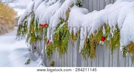 Wooden Fence With Festive Garland Covered In Snow