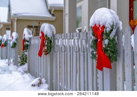 Wreaths With Ribbons On A Snowy Fence In Winter