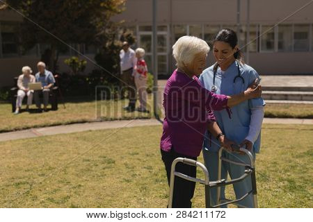 Front view of young female doctor helping disabled senior woman in garden on sunny day