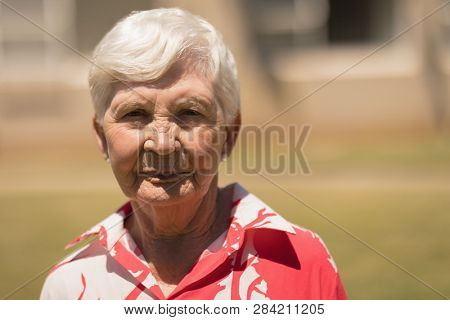 Close-up of serious senior woman looking at camera in the sunshine in garden