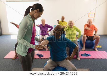 Happy young female trainer assisting senior man in fitness studio