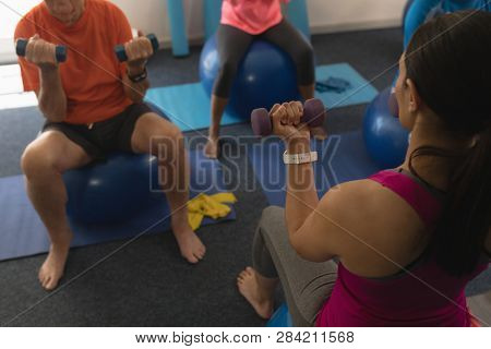 High angle view of senior people exercising with female trainer using dumbbells in fitness studio