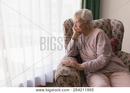 Front view of thoughting senior woman sitting on the couch and looking outside through window at home