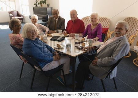 Front view of happy group of senior friends sitting on dining table and looking at camera in home
